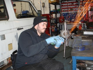 Photo of disabled man welding car parts